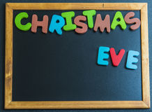 Christmas eve day wooden word on black board Royalty Free Stock Photos