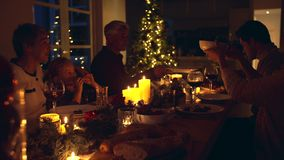 Family having Christmas dinner together. Christmas eve dinner, family of five sitting at dining table talking and having dinner together. Family celebrating stock video footage