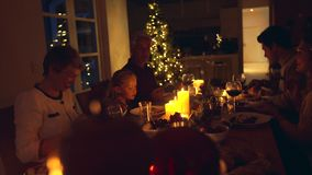 Family enjoying Christmas dinner together. Christmas eve dinner, family sitting at dining table enjoying dinner together. Family celebrating christmas together stock video footage