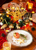 Christmas eve dinner party table setting with decorations. Christmas eve dinner party table setting with lights and gold glittering decorations - elegant white Stock Photo
