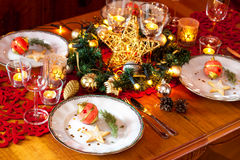 Christmas eve dinner party table setting with decorations. Christmas eve dinner party table setting with lights, gold glittering decorations and elegant white Royalty Free Stock Photo