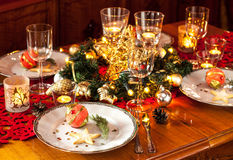 Christmas eve dinner party table setting with decorations. Christmas eve dinner party table setting with lights, gold glittering decorations and elegant white Royalty Free Stock Image