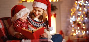 Christmas Eve. family mother and baby reading magic book at home Stock Photography