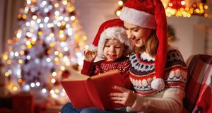 Christmas Eve. family mother and baby reading magic book at home. Near the fireplace and the Christmas tree stock photography