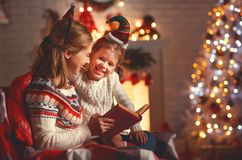 Christmas Eve. family mother and child daughter reading magic bo Royalty Free Stock Photos