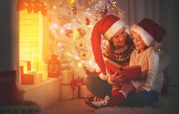 Christmas Eve. family mother and child daughter reading magic bo. Christmas Eve. family mother and child daughter  reading magic book at home near the fireplace Stock Photography