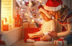 Christmas Eve. family mother and child daughter reading magic bo Stock Photo
