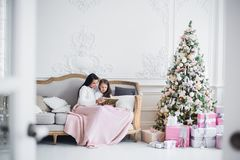Christmas Eve. family mother and child daughter reading magic book at home on a sofa near Christmas tree royalty free stock photos