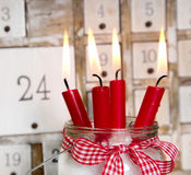 Christmas eve: four red burning candles with a shabby white adve Royalty Free Stock Images