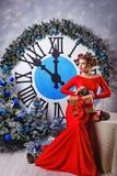 Christmas Eve. Girl near big clock and a Christmas tree. Stock Photo