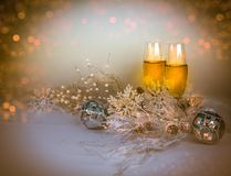 Christmas Eve, New Year Eve background. Picture of two Champagne  glasses with Christmas decorations snowflakes, pine cones, snow pearls and light bokeh Royalty Free Stock Photography