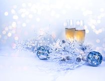Christmas Eve, New Year Eve background. Picture of two Champagne  glasses with Christmas decorations snowflakes, pine cones, snow pearls and light bokeh Stock Photos