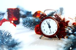 Christmas Eve and New Years clock. At midnight with frosty fir tree branches covered with snow stock photography