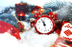 Christmas Eve and New Years clock. At midnight with frosty fir tree branches covered with snow stock image
