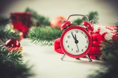 Christmas Eve and New Years clock. At midnight with fir tree branches covered with snow. Vintage toned image stock images