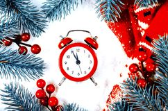 Christmas Eve and New Years clock. At midnight with frosty fir tree branches covered with snow royalty free stock image