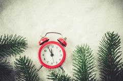 Christmas Eve and New Years clock on snow. Christmas Eve and New Years clock at midnight with fir tree branches on snow. Vintage toned image royalty free stock images