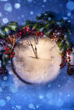 Christmas Eve and New Years at midnight. New Years clock and fir branches covered with snow stock image