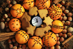 Christmas Eve and New Years at midnight. Christmas clock and oranges, spices and nuts stock photography