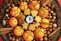 Christmas Eve and New Years at midnight. Christmas clock and oranges, spices and nuts royalty free stock photography