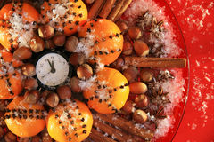 Christmas Eve and New Years at midnight. Christmas clock and oranges, spices and nuts covered with snow royalty free stock image