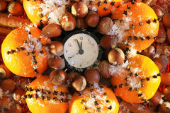 Christmas Eve and New Years at midnight. Christmas clock and oranges, spices and nuts covered with snow stock images