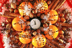 Christmas Eve and New Years at midnight. Christmas clock and oranges, spices and nuts covered with snow stock photo