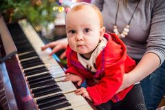 Christmas eve party  baby boy playing piano with his mother