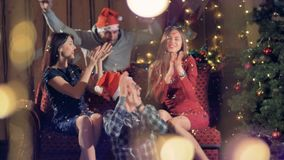 Two couples sit near a Christmas tree and play with confetti. stock video footage