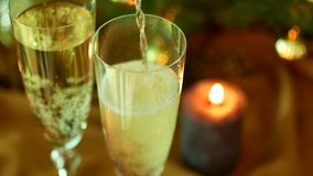 Christmas Eve. Pour champagne over the glasses. A Christmas tree and a candle on the background. stock video footage