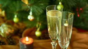 Christmas Eve. Pour champagne over the glasses. A Christmas tree and a candle on the background. Christmas Eve. Pour champagne over the glasses. A Christmas stock footage