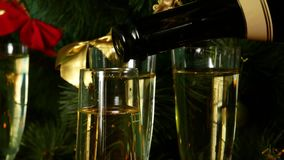 Christmas Eve. Pour champagne over the glasses. A Christmas tree and a candle on the background. stock video