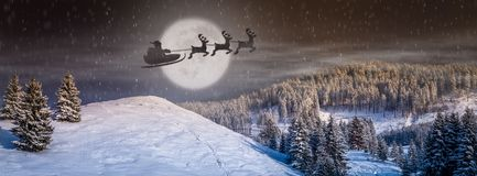 Christmas eve scene with tree, snow falling, Santa Claus in a sleigh with Reindeers flying in the sky