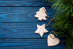 Christmas eve set with spruce branches and tree, heart and star toys on blue wooden background top veiw mock-up Stock Photography