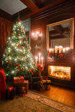 Christmas evening by candlelight. classic apartments with a white fireplace, decorated tree, sofa, large windows and Royalty Free Stock Image