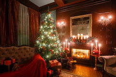 Christmas evening by candlelight. classic apartments with a white fireplace, decorated tree, sofa, large windows and. Christmas Eve by candlelight. classic Stock Photography