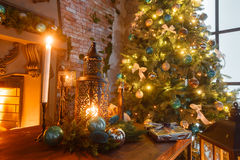 Christmas evening by candlelight. classic apartments with a white fireplace, decorated tree, sofa, large windows and Royalty Free Stock Images