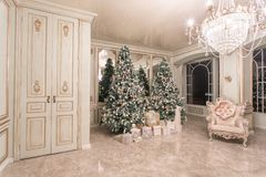 Christmas evening. classic luxurious apartments with decorated christmas tree. Living hall large mirror, chair, high. Windows, columns and stucco royalty free stock image