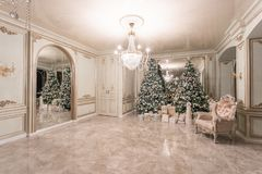 Christmas evening. classic luxurious apartments with decorated christmas tree. Living hall large mirror, chair, high. Windows, columns and stucco royalty free stock images