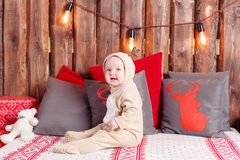 Christmas evening. Little girl sitting. coverall-reindeer costume Royalty Free Stock Images