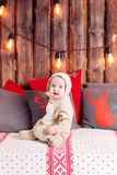 Christmas evening. Little girl sitting. coverall-reindeer costume Royalty Free Stock Photography