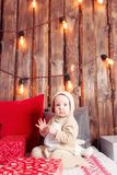 Christmas evening. Little girl sitting and unwraps gifts. coverall-reindeer costume Royalty Free Stock Photo