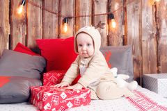 Christmas evening. Little girl sitting and unwraps gifts. coverall-reindeer costume Stock Photos