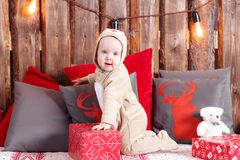Christmas evening. Little girl sitting and unwraps gifts. coverall-reindeer costume Stock Images