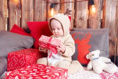Christmas evening. Little girl sitting and unwraps gifts. coverall-reindeer costume Stock Photo