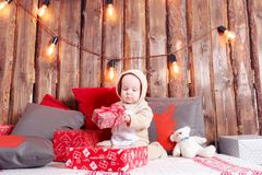 Christmas evening. Little girl sitting and unwraps gifts. coverall-reindeer costume Royalty Free Stock Photos