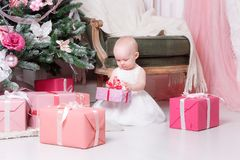 Christmas evening. Little girl sitting and unwraps gifts. white dress Princess Royalty Free Stock Photography
