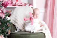 Christmas evening. Little girl sitting and unwraps gifts. white dress Princess Stock Photo