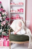 Christmas evening. Little girl sitting and unwraps gifts. white dress Princess Stock Photography
