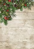 Christmas evergreen branches and holly on wood background. Christmas border of evergreen twigs, holly and cones on a vintage wooden background with a place for royalty free stock photos